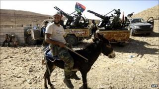 A Libyan fighter loyal to the National Transitional Council (NTC) rides a donkey at an outpost in Wadi Dinar in the area along the frontline with the town of Bani Walid on September 11, 2011.
