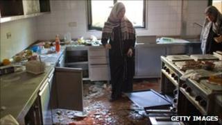 Women tour the plundered kitchen in Col Gaddafi's Baba al Azizia compound on 27 August 2011