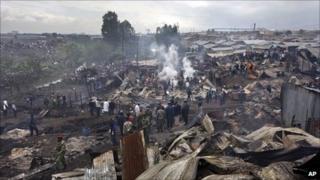 People pick through smouldering rubble in Sinai slum, Nairobi, Kenya (12 Sept 2011)