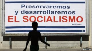 "Boy crosses a street near a billboard in Havana, saying ""we will preserve and develop socialism"" on 3 August, 2011."