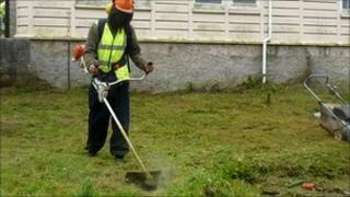 Man strimming grass as part of Redruth North Partnership