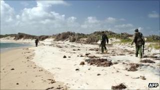 Armed policemen patrol a stretch of beach near Kiwayu Safari village