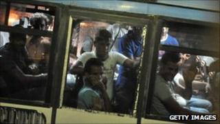 Migrants wait on a bus after arriving in Lampedusa, Italy, 24 August