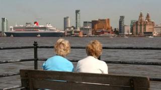 Onlookers watch the Queen Mary 2 ocean liner arrive in Liverpool
