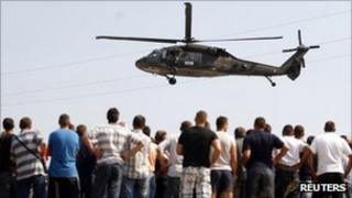 Ethnic Serbs watch a K-For helicopter take off near the Jarinje border crossing, 16 September