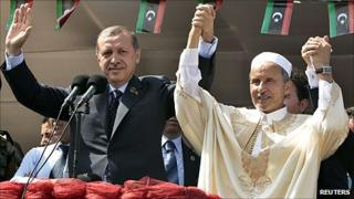 "Turkey's PM Erdogan and Chairman of Libya's NTC Jalil wave to people during a rally at Martyrs"" Square in Tripoli on 16 September"