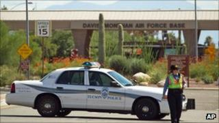 A policewoman in front of a gate of the Davis-Monthan Air Force Base