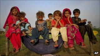 Children, displaced by floods, sit outside their makeshift tent at a roadside in Pakistan's Sindh province