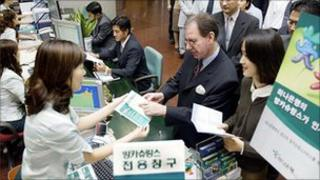 People wait in line at Hana bank in Seoul
