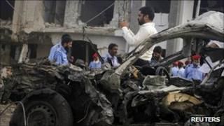 Security officials at the scene of the suicide bomb attack in Karachi on 19 September 2011