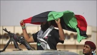 A fighter holds aloft an anti-Gaddafi flag outside Bani Walid, Libya, 19 September 2011