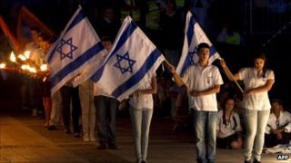Israelis hold their national flag during a one-minute silence on May 8, 2011 to mark Remembrance Day