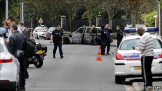 French police stand near the scene of the attack in Orly, with a charred car in the background, 21 August