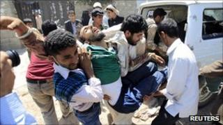 Medics carry a wounded anti-government protester after clashes with security forces in Sanaa September 20, 2011.