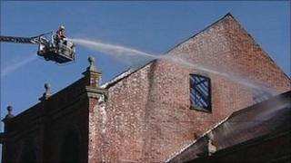A firefighter directs a jet of water from an aerial platform at a disused bingo hall in Shirebrook, Derbyshire
