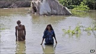 Displaced Pakistanis wade through flood water after fleeing their homes