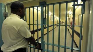 Prison officer locks a prison door