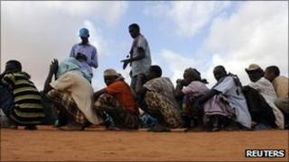 Workers count newly arrived Somali refugees, who wait in a line for the reception centre to open, at Ifo settlement at Kenya's Dadaab refugee Camp