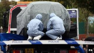 Police forensic officers cover a car