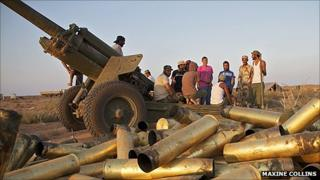 Anti-Gaddafi forces stand next to used artillery munitions
