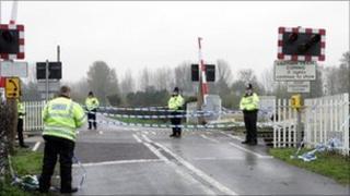 Policemen stand on the level crossing near the scene of a train crash in Ufton Nervet, Berkshire on 7 November 2004