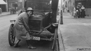 Women cranking up her car in 1916
