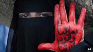 A female protester shows her painted hand which reads: 'Our blood is fuel for our revolution'