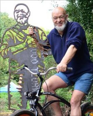 Michael Eavis poses beside a sculpture bench along the cycling route