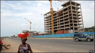 A woman walks past a construction site in Luanda, Angola, in January 2010