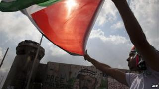 A man waves a Palestinian flag near an Israeli army watchtower at a checkpoint between Jerusalem and Ramallah on 23 September 2011
