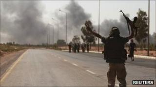 Anti-Gaddafi fighters advance towards Sirte as smoke is seen, around 6km (4 miles) east of Sirte on Monday