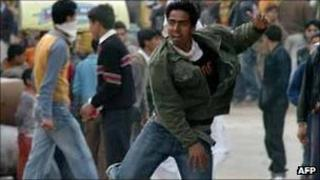 File photo (April 2008) of Kashmiri youths throw stones during a demonstration in Srinagar demand information on the whereabouts of missing persons.