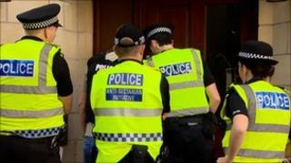 Officers in Pirniefield Bank in Edinburgh during dawn raids