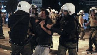 Greek police detain a protester in Athens, 27 September