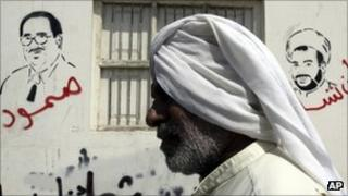 A man passes graffiti of jailed Bahraini opposition figures in Malkiya, Bahrain, 28 September 2011