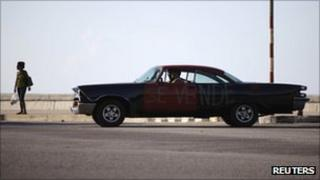 A 1958 Dodge car for sale is driven on Havana's seafront boulevard