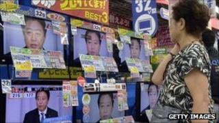 Woman shopper looks at televisions in Tokyo