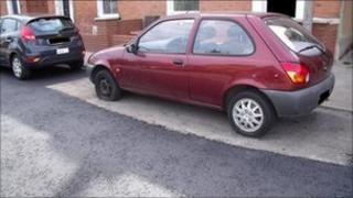 Parked car that has been tarmaced around