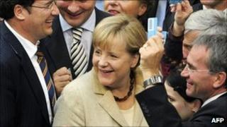German Chancellor Angela Merkel (c) smiles surrounded by MPs holding their ballots on September 29, 2011 at the lower house of German parliament