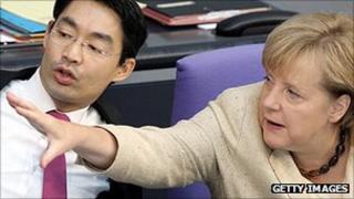 German Economy Minister Philipp Roesler speaks with Chancellor Angela Merkel, 29 September