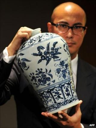 The head of Sotheby's Chinese Ceramics Department, Nicholas Chow, displaying a Ming Dynasty blue and white vase with fruit sprays