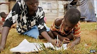 A mother helps her ten-year old son Kennedy Mugonda with his school works outside their home in Hatcliffe on the outskirts of the Zimbabwean capital, Harare, in 2007.