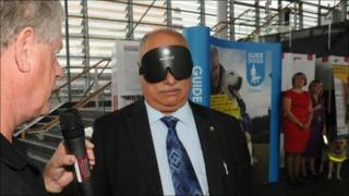 Conservative AM Mohammed Asghar wears a blindfold in the Senedd