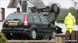 Car turned on its roof beside another car