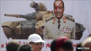 Protesters walk past a placard depicting Field Marshal Mohamed Tantawi in Cairo, 30 September 2011.