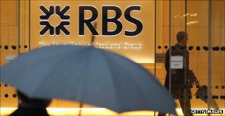 Man with umbrella walks past an RBS bank