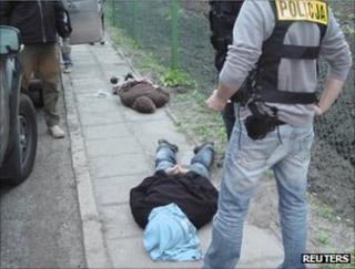Polish police guard the two Ikea bombing suspects after their arrest in the Kujawsko Pomorskie region, 5 October