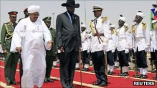 Sudan President Omar al-Bashir, left, welcomes South Sudan President Salva Kiir, at Khartoum airport on 8 October 2011