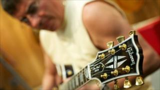Billy Jack tests a Gibson Les Paul guitar in a Nashville shop