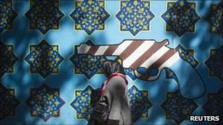 An Iranian woman walks past an anti-US mural on the wall of the former U.S. embassy in Tehran on 12 October 2011